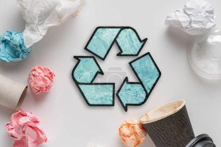 Photo pour Symbole ou icône de recyclage, vue du dessus plat posé avec quelques ordures - image libre de droit