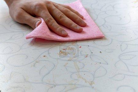 Photo pour Main avec un chiffon rouge essuyant la surface de la table sale dans la cuisine à la maison - image libre de droit