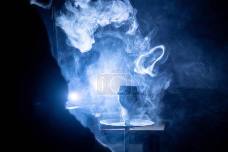 Photo pour L'endroit narguilé avec beaucoup de fumée dans la chambre noire - image libre de droit