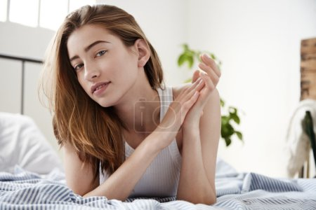 woman touches her hands lies on the bed