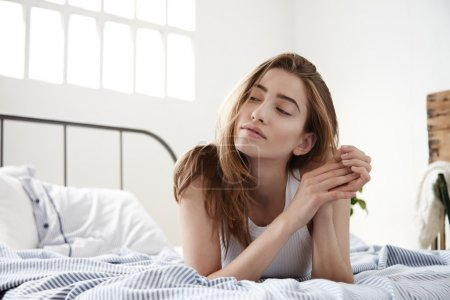 thinking woman watching aside lies in the bed