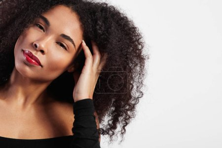 Black woman with afro hair touches it