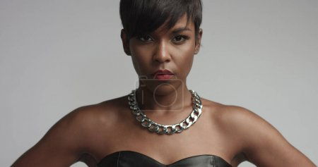 mixed race black woman in black eather dress in studio shoot