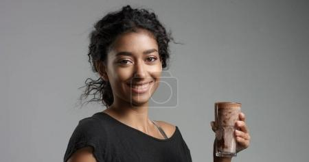 Laughing attractive Middle Eastern girl in relaxed black top drinking mocca, hot chocolate, caffee from a tall glass