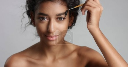 Pretty young girl with flawless skin brushing her eyebrow