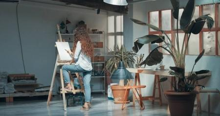 Cute red-haired girl paints in her studio