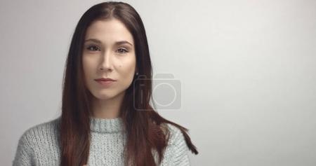 spanish woman sreaching and touching her straight dark hair