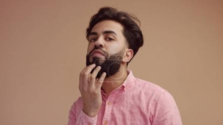 Photo for Man touches his hair an looking at camera. Good groomed man with beard - Royalty Free Image