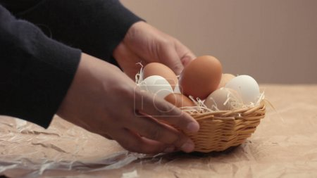 man takes eggs from the basket and put it to the baxoes