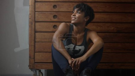 young fit and tone up woman sits lean on wooden wardrobe during workout rest