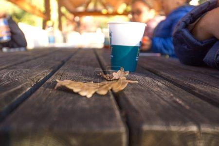 Photo pour Vue rapprochée de la table en bois avec verre en papier - image libre de droit
