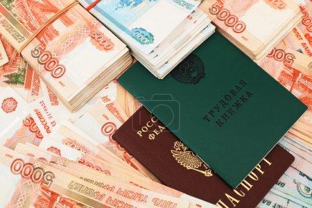 Photo pour Livre de travail (antécédents professionnels) et passeport de la Fédération de Russie avec piles de billets russes - image libre de droit