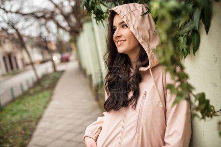 Photo pour Portrait d'une jeune fille heureuse se tenant debout dans la rue pendant une journée pluvieuse et regardant dans la rue - image libre de droit