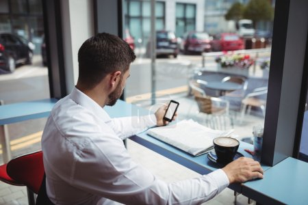 Man using phone while having coffee