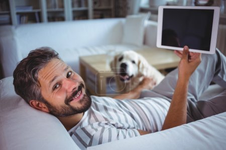 Man holding digital tablet in living room