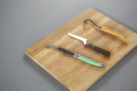 Cheese cutting tools on wooden board