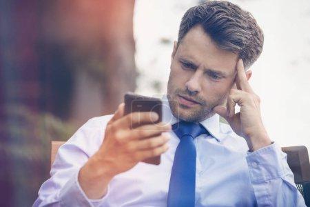Tensed businessman using mobile phone