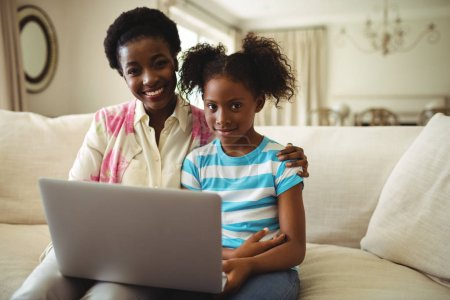 Portrait of mother and daughter using laptop in living room