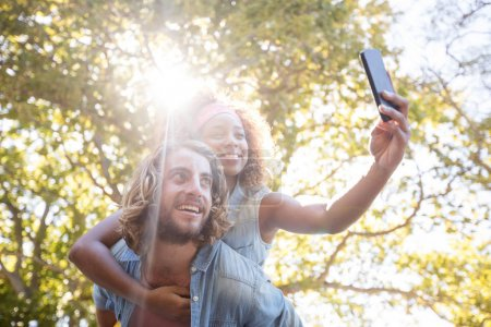 Couple taking selfie while enjoying piggyback ride