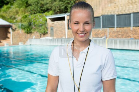 Smiling female coach standing near poolside