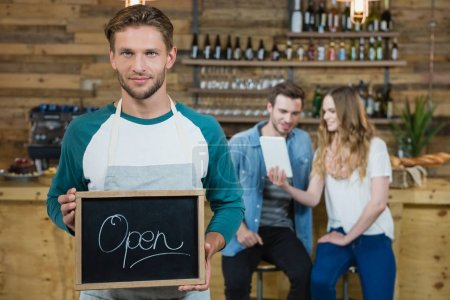 Waiter holding chalkboard with open sign