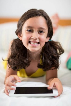 smiling girl with digital tablet lying on bed