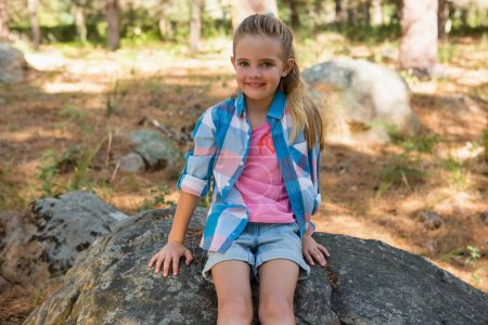 girl sitting on the rock in forest