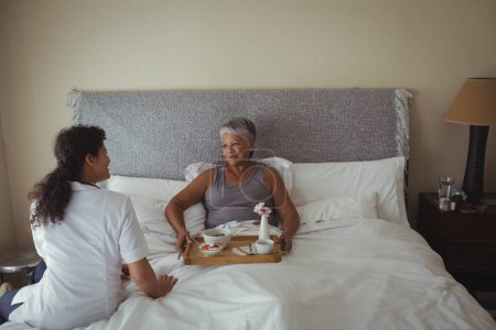 doctor serving breakfast to woman on bed
