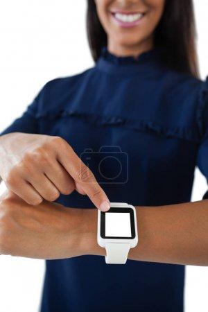 Female executive operating smartwatch