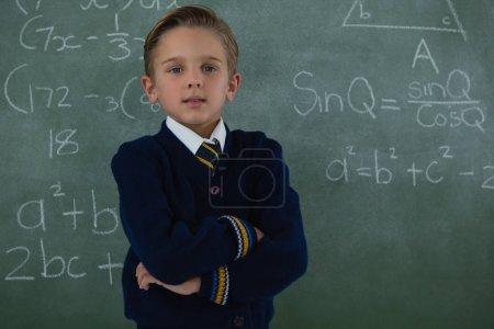 Schoolboy standing arms crossed