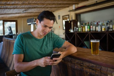 Man using phone while sitting at bar counter