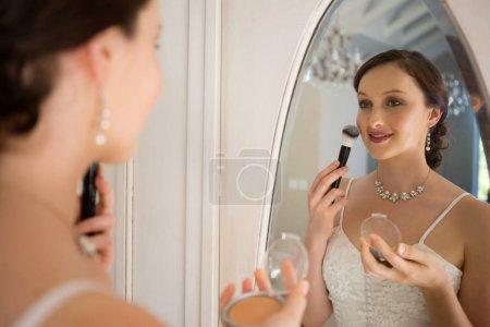 bride applying makeup reflecting on mirror