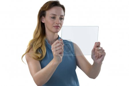 Female executive using glass tablet
