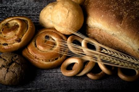 Different types of fresh bread and wheat spikes on old wooden ta