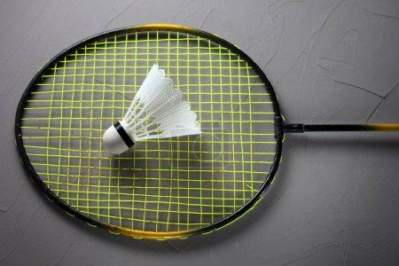 Photo pour Shuttlecock pour jouer au badminton couché sur une raquette fond concret - image libre de droit