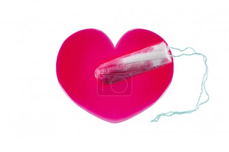 New unused tampon on heart shaped red syrup liquid that looks like blood