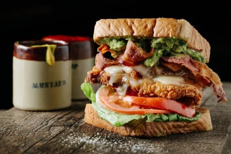 Photo for BLT sandwich with fried chicken and avocado on dark background - Royalty Free Image