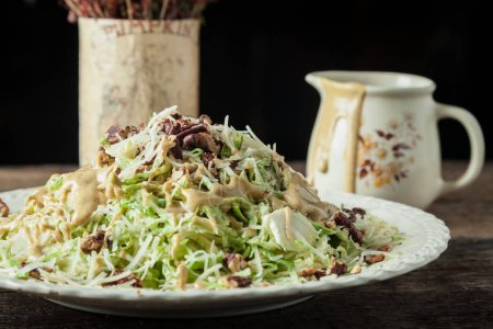 Photo for Gourmet caesar with lettuce, shredded parmesan, toasted pecans and mustard vinaigrette - Royalty Free Image