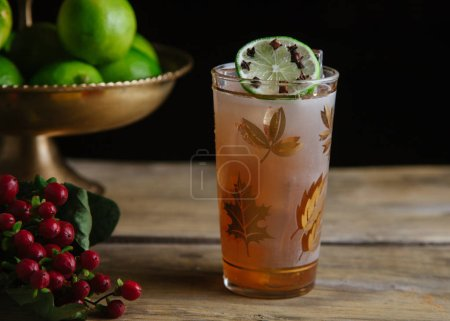 Photo for Fall alcoholic beverage in a tall pint glass garnished with limes on rustic background - Royalty Free Image
