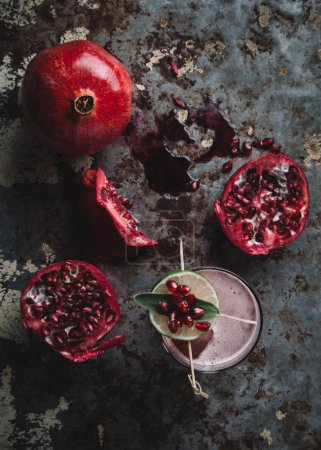 Photo for Alcoholic cocktail garnished with pomegranate seeds on dark moody background - Royalty Free Image