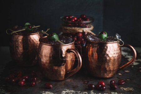 Moscow Mule cocktails garnished with cranberries and lime