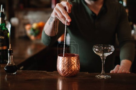 Photo for Mixologist bartender creating a cocktail at a bar - Royalty Free Image