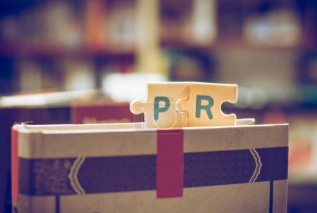 Photo pour Lettres de puzzle PR. Word PR sur les livres en librairie . - image libre de droit