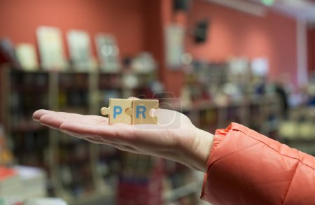 Woman holds puzzle word PR