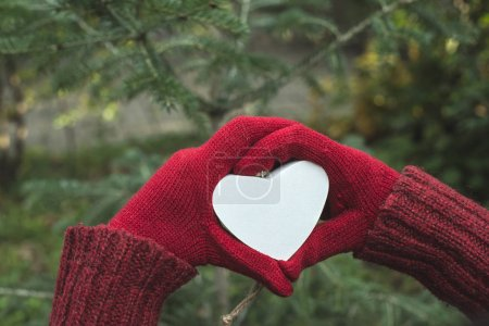 Hands in gloves and white heart