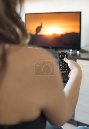 Woman hold TV remote control.