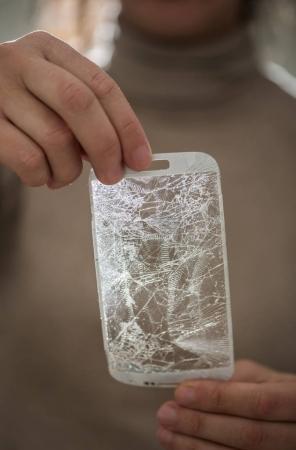 Hands holding a broken screen of smartphone