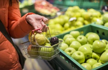 Buying apples and pears in shop.