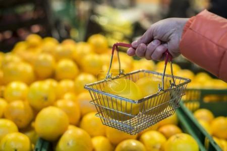 Buying oranges in shop.