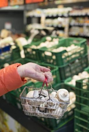 Buying mushrooms in shop.